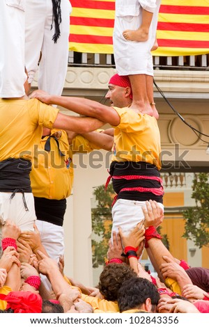 TIANA, SPAIN - SEPTEMBER 18: Unidentified people of Castellers de Badalona team do a Castell or human tower, typical tradition in Catalonia, on September 18, 2011, in Tiana, Barcelona, Spain.
