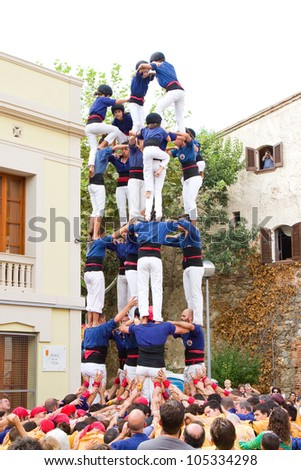 TIANA, SPAIN - SEPTEMBER 18: Unidentified people of Castellers de Mataro team do a Castell or human tower, typical tradition in Catalonia, on September 18, 2011, in Tiana, Barcelona, Spain.