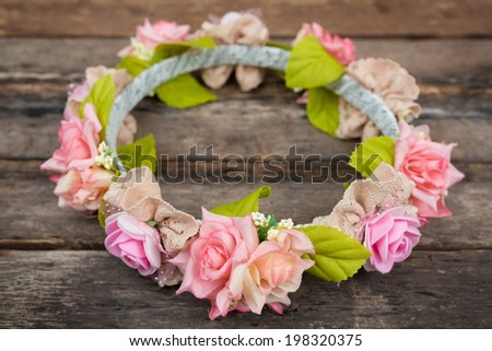 tiara of artificial roses on wooden background