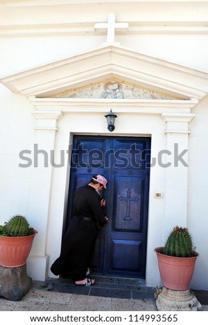 TIBERIAS - MAY 19:A Greek orthodox priest open the door to the Greek Orthodox Church of the Seven Apostles In Capernaum located at the shore of the Sea of Galilee Israel on May 19 2009.