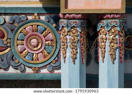 Tibetan buddhist ornamented pillars and Chackra wheel in the background. Stock photo ©