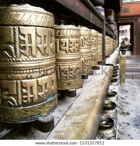 """Tibetan Buddhist Prayer wheels inscribed with sanskrit lettering  """"om mani padme hum"""" meaning """"in the lotus made of jewels"""" in a temple in Kathmandu, Nepal"""