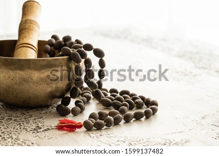 Tibetan music bowl  with mala beads on white concrete background with copy space. Essential accessory for mindfulness or meditation. Stock photo ©