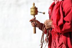 Tibetan prayer wheel in hand of old Bhutanese prayer, Thimphu, Bhutan. (Selective focus)