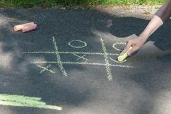 Tic-tac-toe chalk game on asphalt, drawing on the sidewalk.