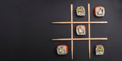 Tic tac toe game with sushi on dark black background, creative concept sushi rolls. Banner, playing tic tac toe game. Japanese cuisine concept, sushi advertisement.