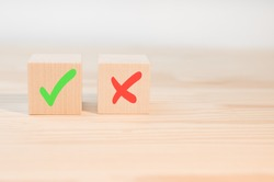 Tick mark and cross mark x on wooden cubes. Wooden blocks with green check mark and red x. Concept of positive or negative decision making or choice of approval or rejection. copy space