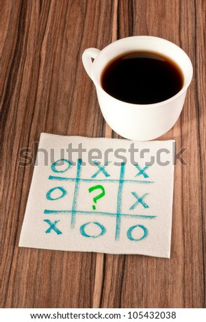 Tick-tack-toe and question mark on a napkin and cup of coffee