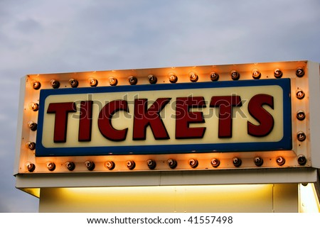 Ticket booth sign illuminated at twilight - stock photo