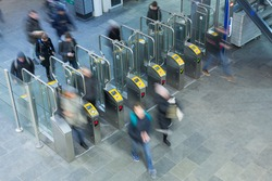 Ticket gates at the entrance of a dutch railway station with blurred passengers