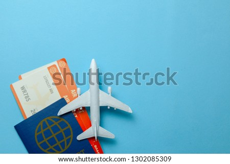 Tickets for plane and passport with model of passenger plane on blue background. Copy space for text.