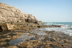 Tidal pools on rocky beach beside rocky cliff face with blue sky