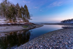Tidal river in Maine at low tide during sunset.