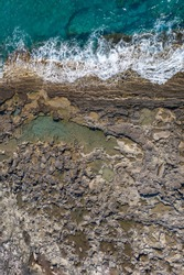 Tide pools during low tide. Rocky sea shore with dramatic texture, vertical top view