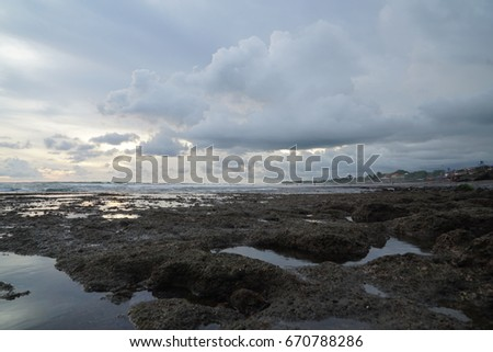 Tide pools illuminated by a setting sun that is being encroached on by a tropical storm in Bali, Indonesia. #670788286