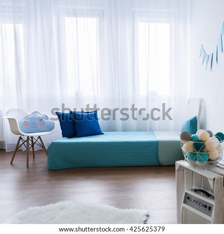 Tidy modern designed room for boy. Blue elements in white room
