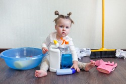 Tidy up concept, stay home, a girl of 1.5 years old sits on the floor and studies bottles with household chemicals, Dangers for children in the home