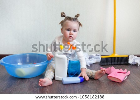 Tidy up concept, stay home, a girl of 1.5 years old sits on the floor and studies bottles with household chemicals, Dangers for children in the home  Foto stock ©