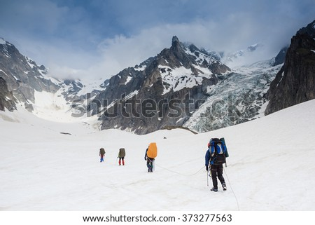 Tied climbers climbing mountain with snow field #373277563