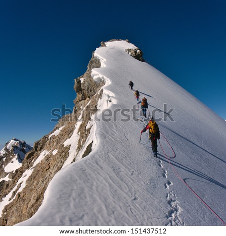 Tied climbers climbing mountain with snow field tied with a rope with ice axes and helmets #151437512