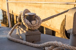 Tied rope knot on metallic bollard , seafaring port. Nautical ship moored in dock. Anchor rope in the port, ship mooring tool.