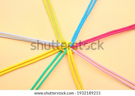 Tied ropes on color background. Unity concept