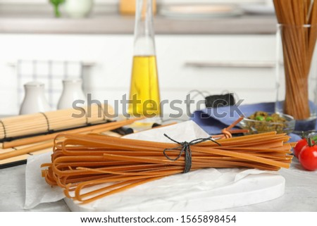Tied uncooked buckwheat noodles on kitchen table