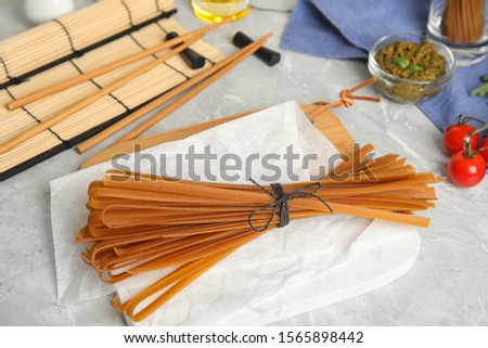 Tied uncooked buckwheat noodles on light grey table