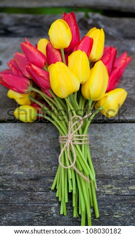 tied yellow and red tulips on wooden surface