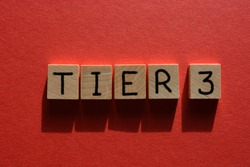 Tier 3, coronavirus alert levels, word in wooden alphabet letters isolated on red background