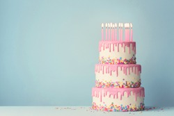 Tiered birthday cake with drip frosting and twelve candles