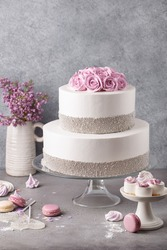 Tiered cake for wedding or birthday. Beautiful festive white cake decorated with cream roses and silver beads over gray concrete background. Side view