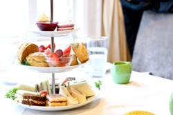 tiered cake stand with finger foods and sweets to accompany afternoon tea at a hotel