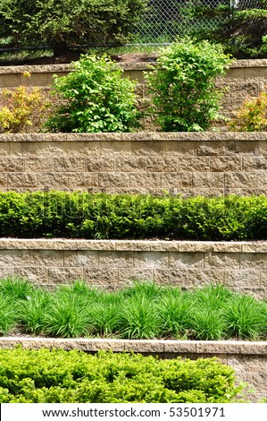Tiered Retaining Wall with Plants and Shrubs - stock photo