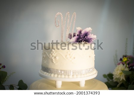 Tiered Wedding Cake with M on Top and Purple Flower Photo stock ©