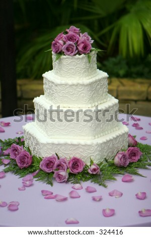 stock photo Tiered wedding cake with white frosting and purple flowers