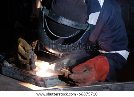 TIG welder uses torch to make sparks during manufacture of metal equipment.