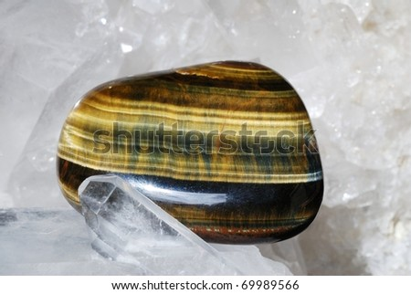 Tiger eye gem energized on druze of quartz crystals. This gem is used as a jewel stone and also in alternative medicine and esoterics (connected with 3rd chakra).