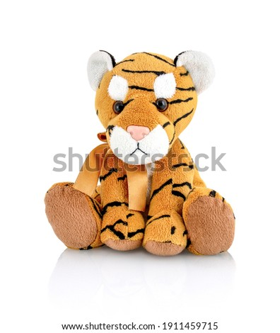 Tiger plushie doll isolated on white background with shadow reflection. Playful bright brown puppy toy. Plush stuffed puppet on white backdrop. Fluffy toy for children. Cute furry plaything for kids. ストックフォト ©