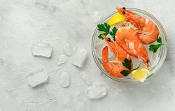 Tiger prawns in a bowl with ice, lemon and parsley on grey background. Above, copy space.