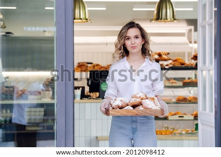 Tight lipped blond woman posing with a tray full of pastry in a doorstep of her shop. She's wearing dress shirt and light jeans, looking at the camera. Stock photo ©