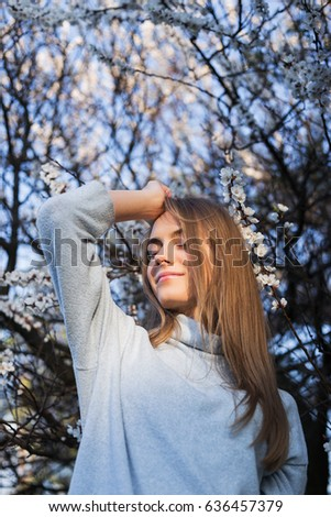Tight medium shot beautiful woman with long blond hair touches her hair and  looking at camera. Young model stands in park on blossom trees background. She dressed in white pullover. Medium Close-Up.