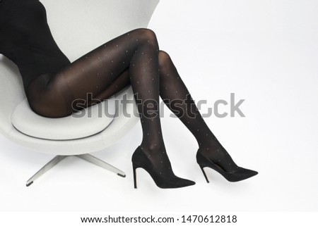 Tights. Black covering tights. Female legs in shoes on a stiletto dressed in tights