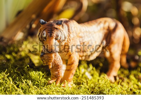 Tigress with a baby between her teeth. Tiger toy figurine in situation on defocused nature background.