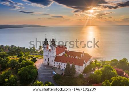 Tihany, Hungary - Aerial skyline view of the famous Benedictine Monastery of Tihany (Tihany Abbey) with beautiful colourful sky and clouds at sunrise over Lake Balaton Stock photo ©