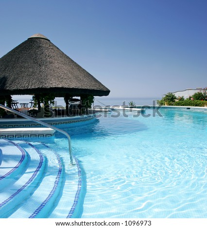 Tiki hut and bar by steps of swimming pool of luxury hotel on a bright sunny day in Spain