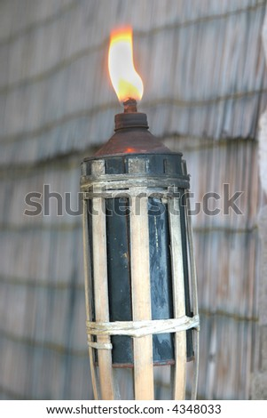 tiki torch lit on a rustic background