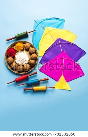 Til Gul OR Sweet Sesame Laddu with Miniature Fikri and Kite model with haldi Kumkum and sugar crystals for Makar Sankranti festival over moody background, selective focus  #782502850