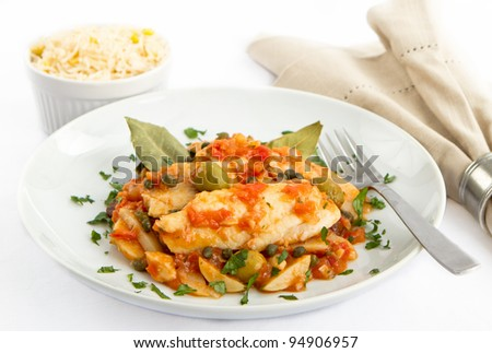Tilapia fish prepared Veracruz style with tomatoes, potatoes, capers and olives