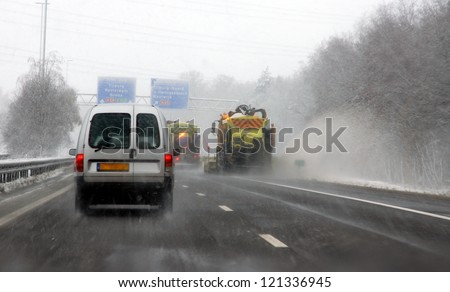 TILBURG, NETHERLANDS -Â?Â? DECEMBER 7 : Code orange because of heavy snowfall makes driving on the highway's very difficult on dec. 7, 2012 Tilburg, Netherlands.Snow ploughs  are cleaning the road . - stock photo